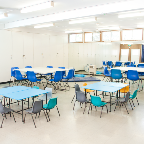 Interior of Nellie Hall showing tables and chairs set up for a meal, craftgroup or playgroup.